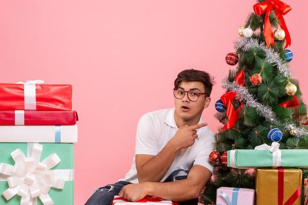Vooraanzicht jonge man rond cadeautjes en kerstboom op de roze achtergrond Gratis Foto