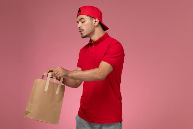 Vooraanzicht jonge mannelijke koerier in rode uniforme kaap houden papier voedselpakket op roze bureau. Gratis Foto