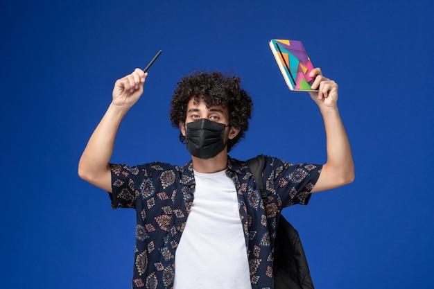 Vooraanzicht jonge mannelijke student die zwart masker met het voorbeeldenboek en de pen van de rugzakholding op de blauwe achtergrond draagt. Gratis Foto