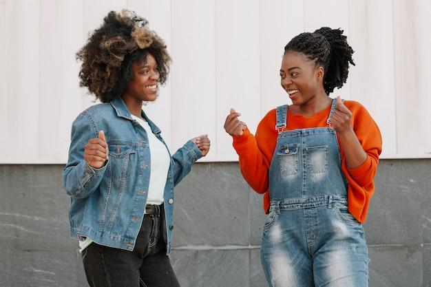 Vooraanzicht jonge meisjes glimlachen naar elkaar Gratis Foto