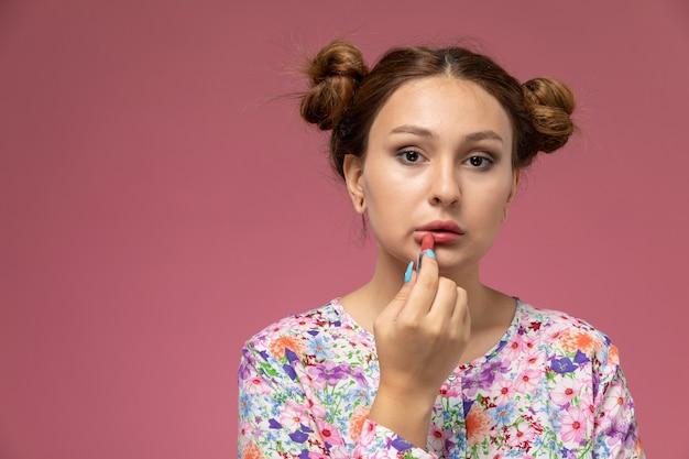 Vooraanzicht jonge mooie vrouw in bloem ontworpen shirt en spijkerbroek make-up op het roze bureau doen Gratis Foto