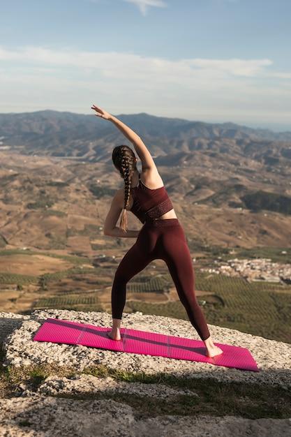 Vooraanzicht jonge vrouw beoefenen van yoga Gratis Foto