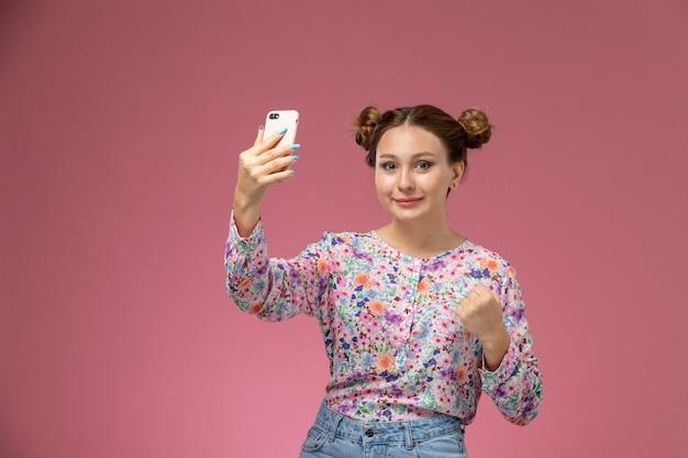 Vooraanzicht jonge vrouw in bloem ontworpen shirt en spijkerbroek een selfie met glimlach op roze achtergrond Gratis Foto