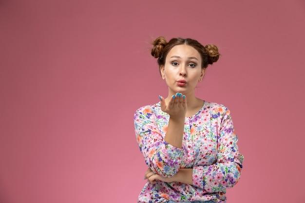 Vooraanzicht jonge vrouw in bloem ontworpen shirt en spijkerbroek lucht kussen verzenden op de roze achtergrond Gratis Foto