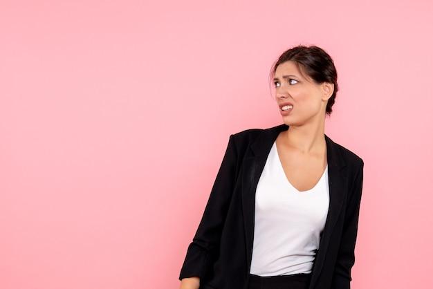 Vooraanzicht jonge vrouw in donker jasje ontevreden op roze achtergrond Gratis Foto