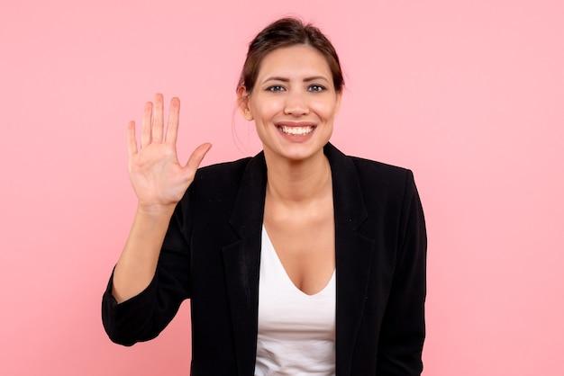 Vooraanzicht jonge vrouw in donkere jas groet met glimlach op roze achtergrond Gratis Foto