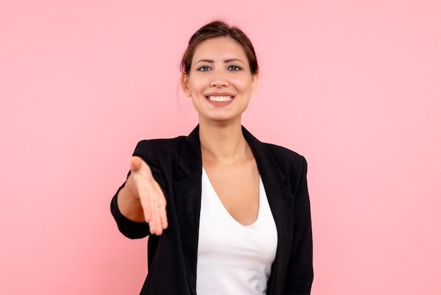 Vooraanzicht jonge vrouw in donkere jas groet op een roze achtergrond Gratis Foto