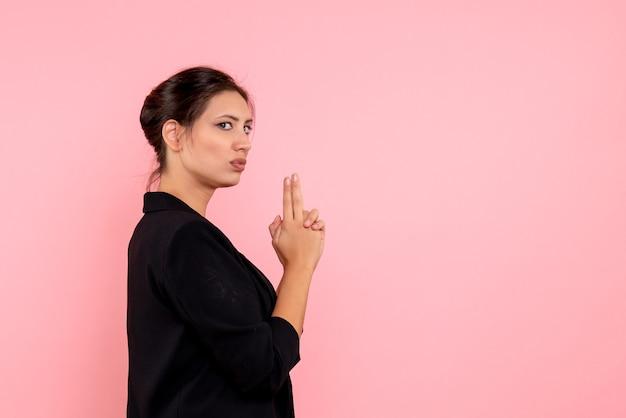 Vooraanzicht jonge vrouw in donkere jas in pistool houden pose op roze achtergrond Gratis Foto