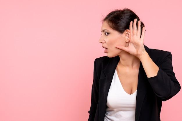 Vooraanzicht jonge vrouw in donkere jas luisteren op de roze achtergrond Gratis Foto