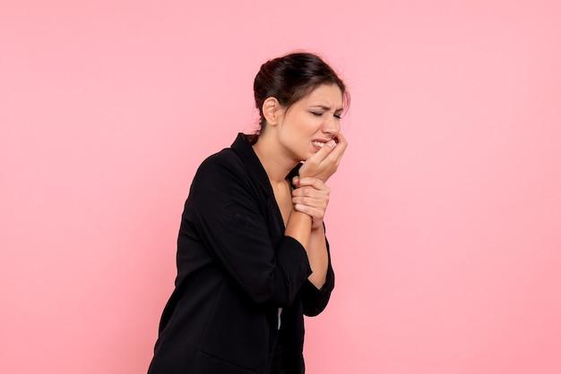 Vooraanzicht jonge vrouw in donkere jas met kiespijn op roze achtergrond Gratis Foto