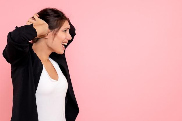 Vooraanzicht jonge vrouw in donkere jas nerveus op roze achtergrond Gratis Foto