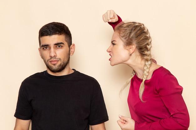 Vooraanzicht jonge vrouw in rood shirt probeert een man in elkaar te slaan op de crèmekleurige ruimte vrouwelijke doek foto geweld huiselijk Gratis Foto