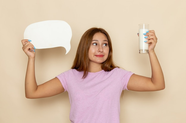 Vooraanzicht jonge vrouw in roze t-shirt en spijkerbroek met wit bord en melk op grijs Gratis Foto