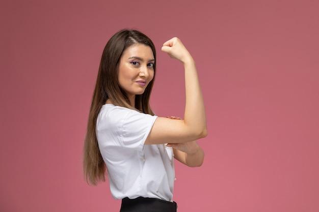 Vooraanzicht jonge vrouw in wit overhemd glimlachend en buigen op roze muur, model vrouw Gratis Foto
