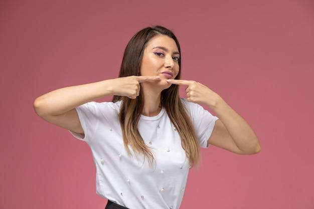 Vooraanzicht jonge vrouw in wit overhemd haar acne aan te raken op roze muur, kleur vrouw pose model Gratis Foto