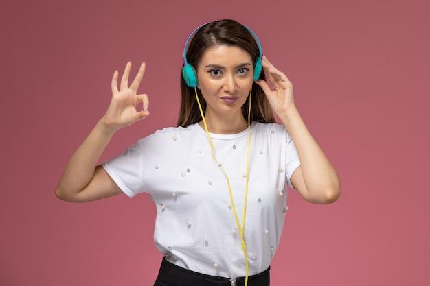 Vooraanzicht jonge vrouw in wit overhemd luisteren naar muziek en poseren op de roze muur, kleur vrouw model Gratis Foto