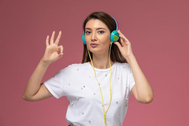 Vooraanzicht jonge vrouw in wit overhemd luisteren naar muziek en poseren op de roze muur, kleur vrouw pose model Gratis Foto