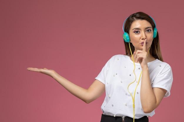 Vooraanzicht jonge vrouw in wit overhemd luisteren naar muziek met stilte teken op de roze muur, model vrouw Gratis Foto