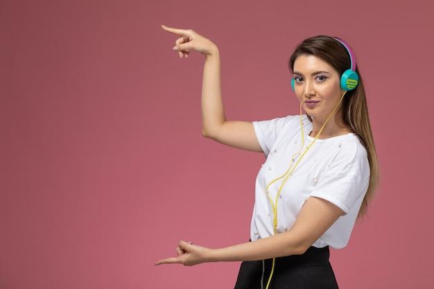 Vooraanzicht jonge vrouw in wit overhemd luisteren naar muziek op de roze muur, kleur vrouw model vrouw Gratis Foto