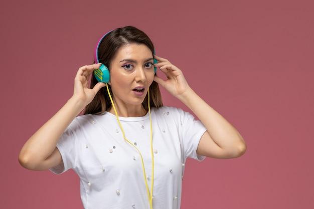 Vooraanzicht jonge vrouw in wit overhemd luisteren naar muziek op roze muur, kleur vrouw model Gratis Foto