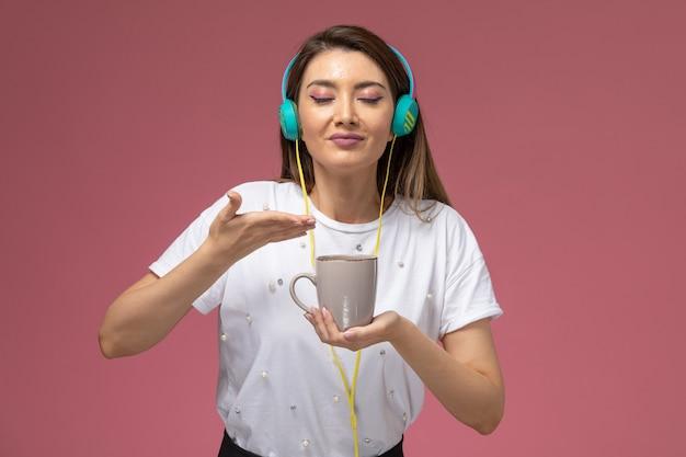 Vooraanzicht jonge vrouw in wit overhemd luisteren naar muziek ruikende koffie op de roze muur, kleur vrouw model vrouw Gratis Foto