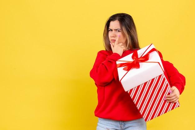 Vooraanzicht jonge vrouw met kerst cadeau denken op gele achtergrond Gratis Foto