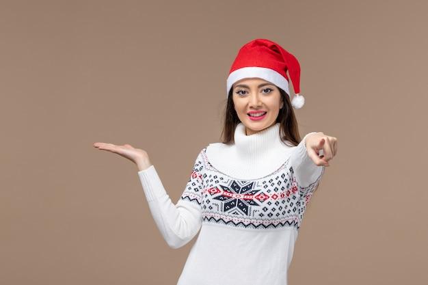 Vooraanzicht jonge vrouw met lachende uitdrukking op bruine achtergrond vakantie emotie kerst Gratis Foto