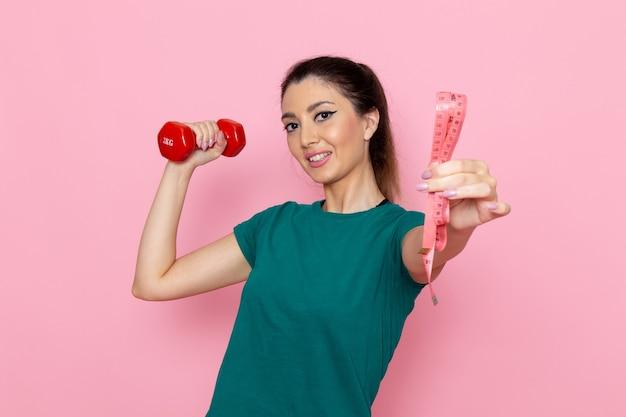 Vooraanzicht jonge vrouw met rode halters op de lichtroze muur atleet sport oefening gezondheid trainingen Gratis Foto