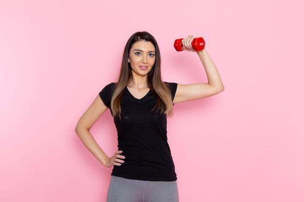 Vooraanzicht jonge vrouw met rode halters op lichtroze bureau atleet sport oefening gezondheid trainingen Gratis Foto