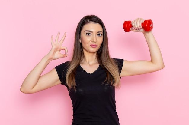 Vooraanzicht jonge vrouw met rode halters op lichtroze muur atleet sport oefening gezondheidstraining Gratis Foto