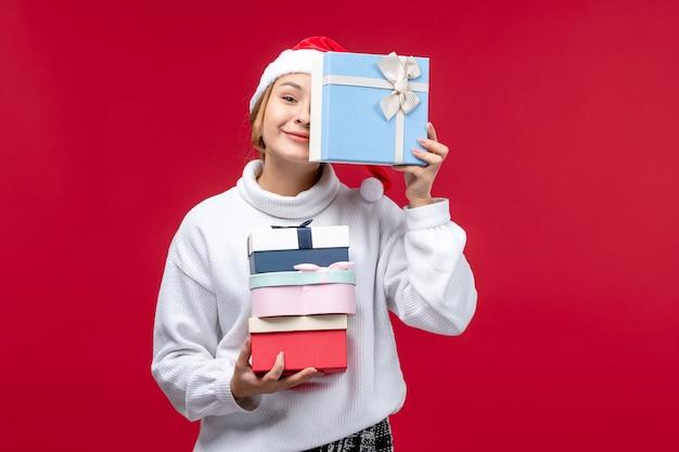 Vooraanzicht jonge vrouw met vakantie presenteert op een rode achtergrond Gratis Foto