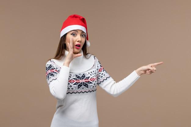 Vooraanzicht jonge vrouw poseren in rode dop op bruine achtergrond emoties kerst-nieuwjaar Gratis Foto