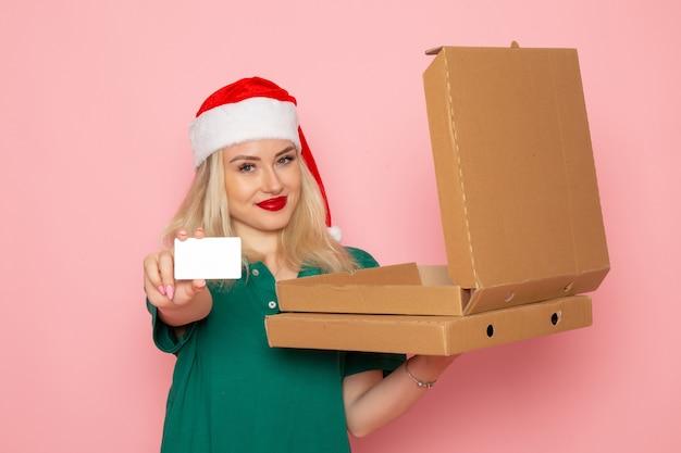 Vooraanzicht jonge vrouwelijke bedrijf bankkaart en pizzadozen op lichtroze muur kleur vakantie xmas nieuwjaar foto baan uniform Gratis Foto