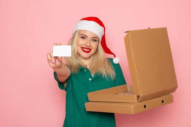 Vooraanzicht jonge vrouwelijke bedrijf bankkaart en pizzadozen op roze muur kleur vakantie nieuwjaar foto baan uniform Gratis Foto