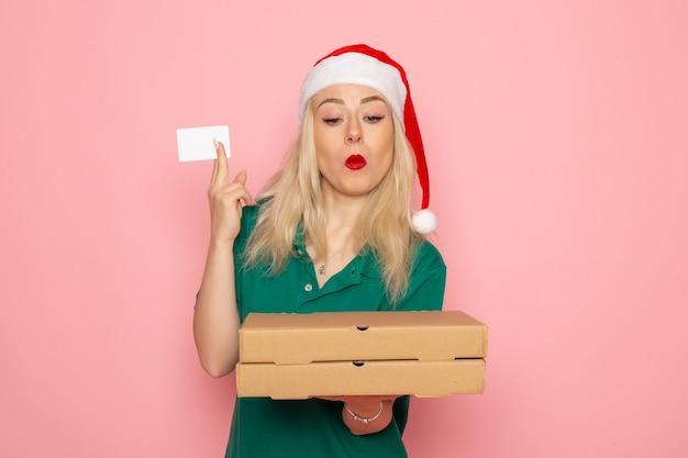 Vooraanzicht jonge vrouwelijke bedrijf bankkaart en pizzadozen op roze muur kleur vakantie xmas nieuwjaar baan uniform Gratis Foto