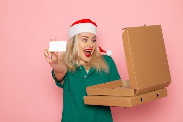 Vooraanzicht jonge vrouwelijke bedrijf bankkaart en pizzadozen op roze muur kleur vakantie xmas nieuwjaar foto baan uniform Gratis Foto