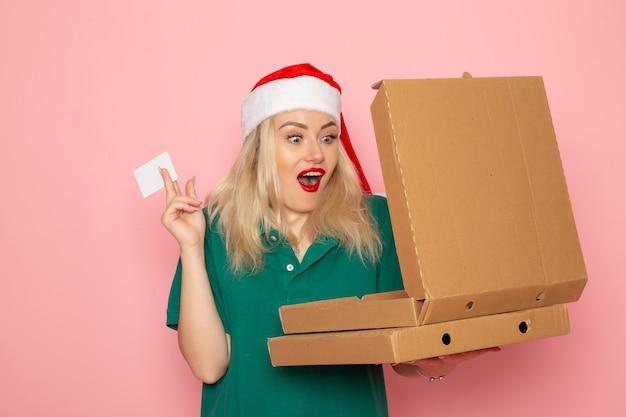 Vooraanzicht jonge vrouwelijke bedrijf bankkaart en pizzadozen op roze muur kleur vakantie xmas nieuwjaar foto uniform Gratis Foto