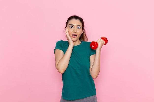 Vooraanzicht jonge vrouwelijke halters op de lichtroze muur atleet sport oefening gezondheid trainingen Gratis Foto