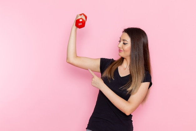 Vooraanzicht jonge vrouwelijke halters op het lichtroze bureau atleet sport oefening gezondheidstraining Gratis Foto