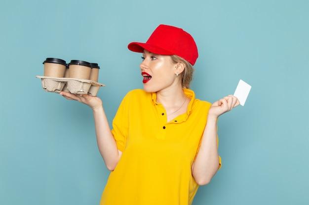Vooraanzicht jonge vrouwelijke koerier in geel overhemd en rode cape met plastic koffiekopjes witte kaart op de blauwe ruimte vrouw Gratis Foto