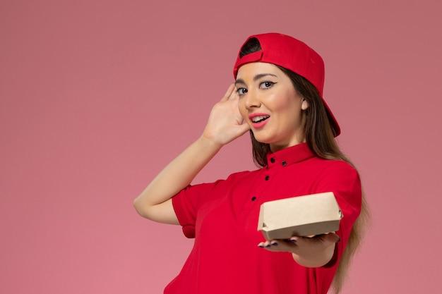 Vooraanzicht jonge vrouwelijke koerier in rood uniform en cape met weinig voedselpakket voor bezorging op haar handen op de roze muur Gratis Foto