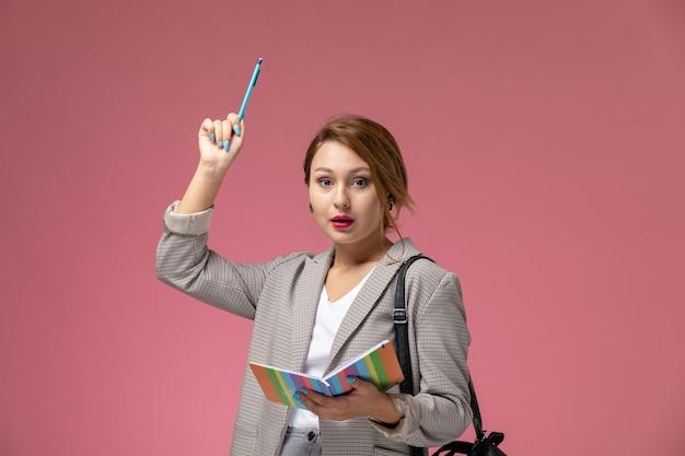Vooraanzicht jonge vrouwelijke student in grijze jas poseren bedrijf voorbeeldenboek met opgeheven pen op de roze achtergrond lessen hogeschool studie Gratis Foto