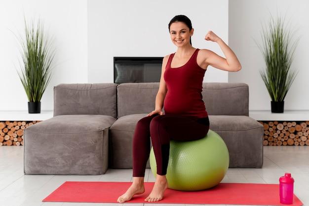 Vooraanzicht jonge zwangere vrouw met behulp van een fitness-bal Gratis Foto