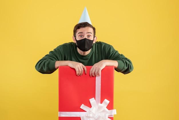 Vooraanzicht jongeman met grote ogen met feestmuts achter grote geschenkdoos op geel Gratis Foto