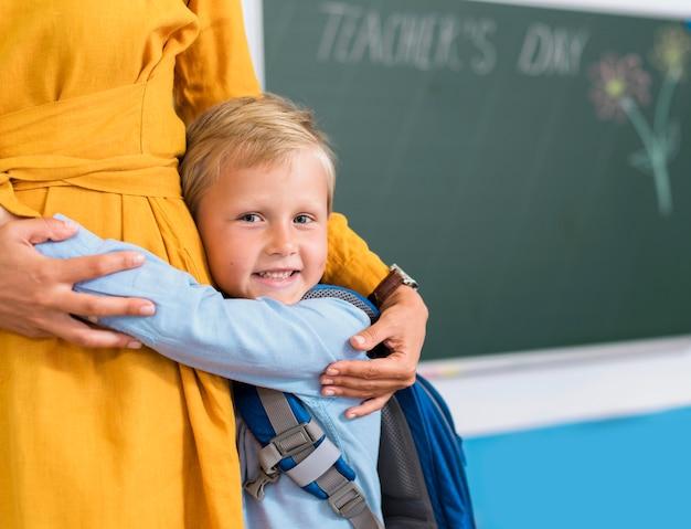 Vooraanzicht jongen knuffelen zijn leraar met kopie ruimte Gratis Foto