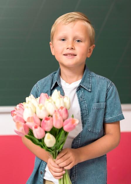 Vooraanzicht jongen met wat bloemen voor zijn leraar Gratis Foto
