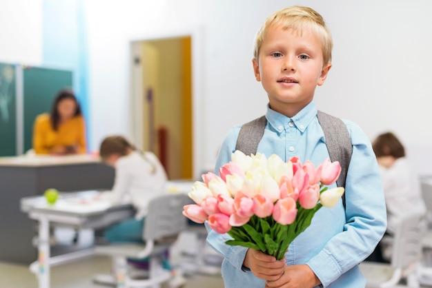 Vooraanzicht jongetje met een boeket bloemen voor zijn leraar Gratis Foto