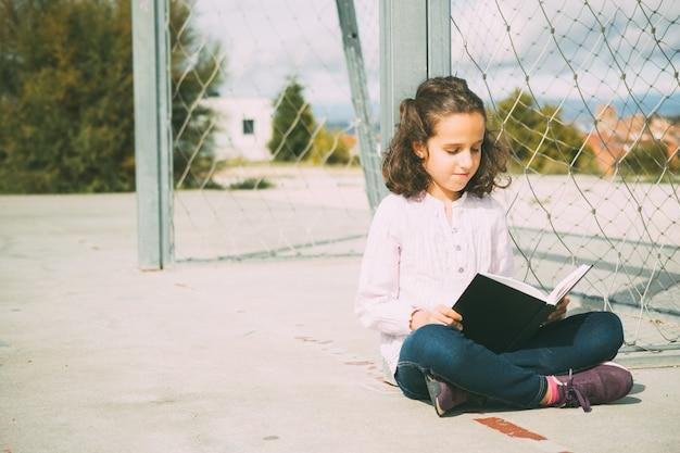 Vooraanzicht kaukasisch meisje met bruin haar, zittend op de vloer tijdens het lezen van een boek op straat Premium Foto
