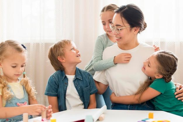 Vooraanzicht kinderen knuffelen hun leraar Gratis Foto