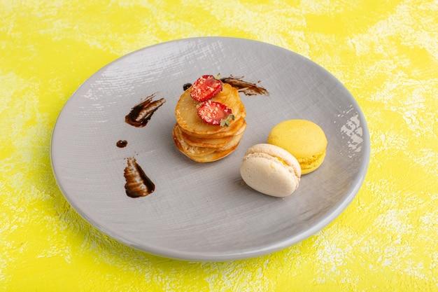 Vooraanzicht kleine gebakjes in plaat met macarons op de gele tafel, bak zoete thee fruit gebak Gratis Foto